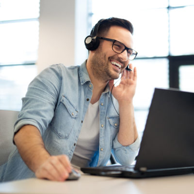 Young smiling male call center operator doing his job with a hea